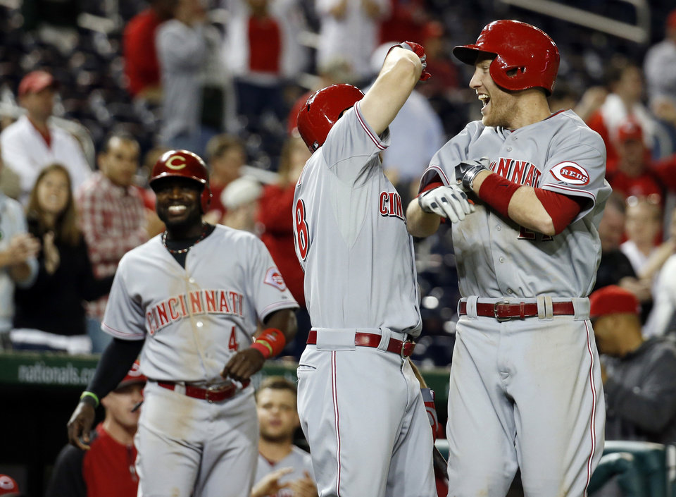 Photo - Cincinnati Reds' Todd Frazier, right, celebrates with Chris Heisey, center, as Brandon Phillips (4) walks near, after Frazier hit a two-run homer during the 15th inning of a baseball game against the Washington Nationals at Nationals Park, Monday, May 19, 2014, in Washington. The Reds won 4-3 in 15 innings. (AP Photo/Alex Brandon)