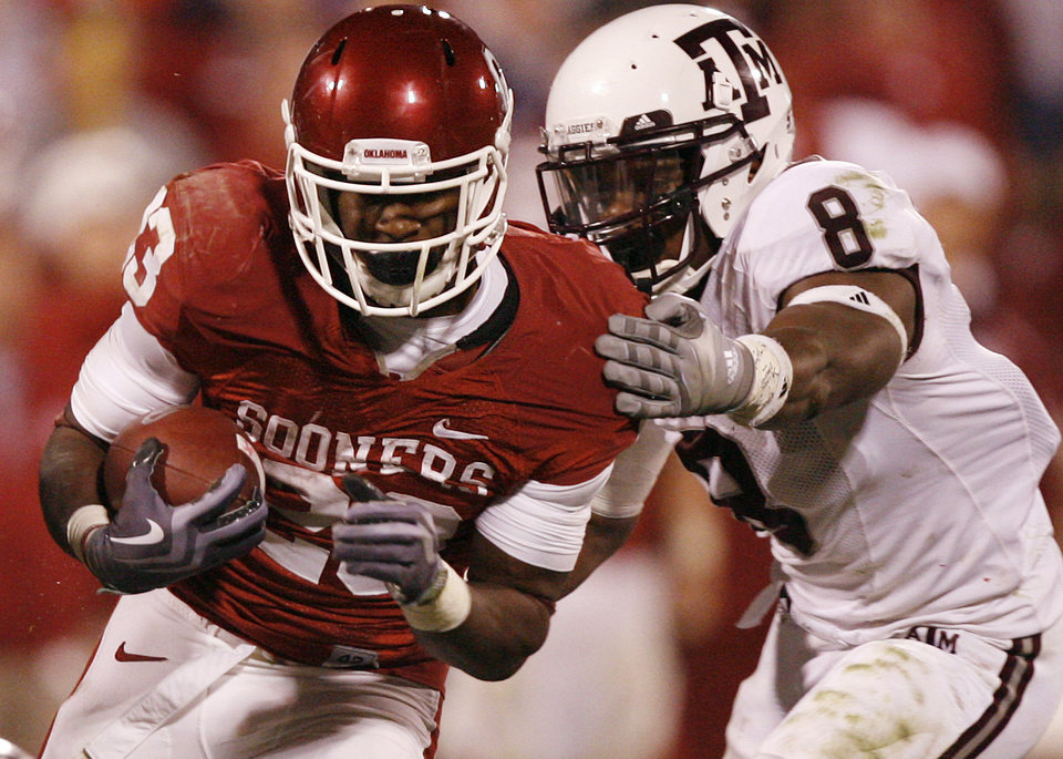 Photo - Oklahoma's Jermie Calhoun (23) runs past Texas A&M's Garrick Williams (8) during the second half of the college football game between the University of Oklahoma Sooners (OU) and the Texas A&M Aggies at Gaylord Family-Memorial Stadium on Saturday, Nov. 14, 2009, in Norman, Okla. 