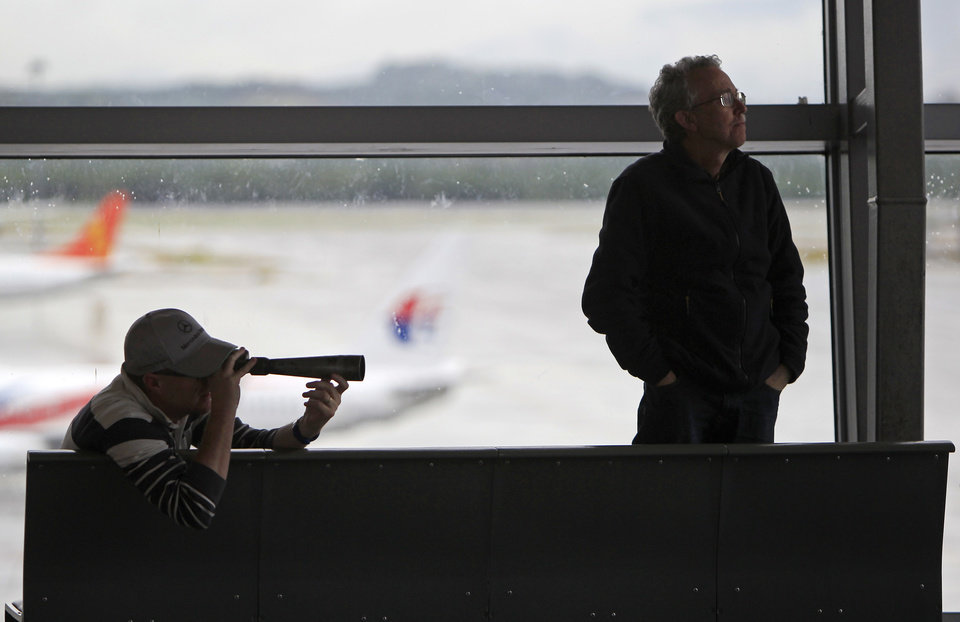 Photo - A man uses a telescope to look at planes at Kuala Lumpur International Airport in Sepang, Malaysia, Tuesday, March 18, 2014. Checks into the background of all the Chinese nationals on board the missing Malaysian jetliner have uncovered no links to terrorism, the Chinese ambassador in Kuala Lumpur said Tuesday. (AP Photo/Lai Seng Sin)