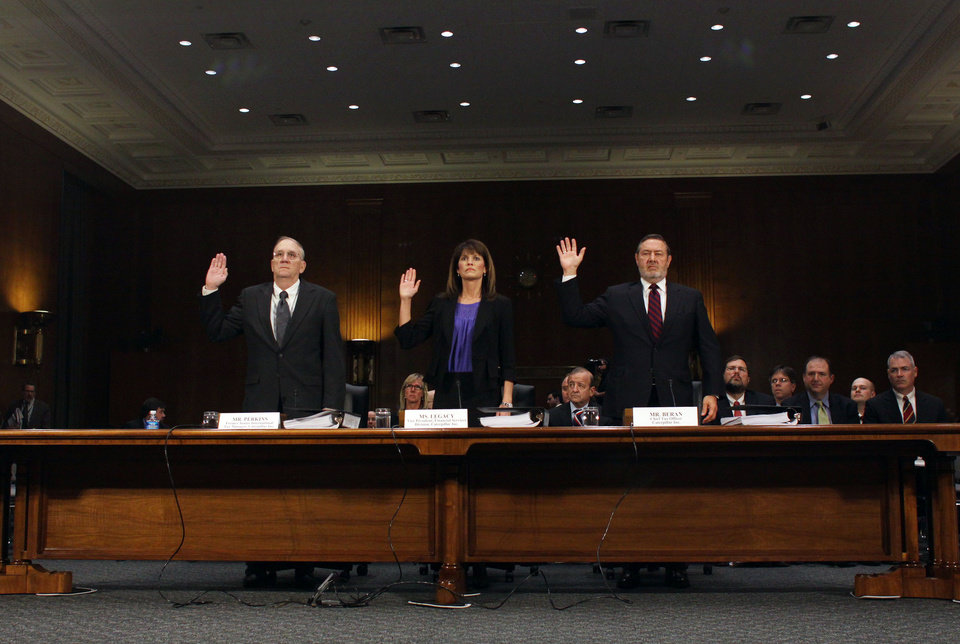 Photo - From left, Rodney Perkins, former Senior International Tax Manager for Caterpillar; Julie Lagacy, Vice President, Finance Services Division of Caterpillar;, and Robin Beran, Chief Tax Officer for Caterpillar, are sworn-in on Capitol Hill in Washington, Tuesday, April 1, 2014, prior to testifying before the Senate Permanent subcommittee on Investigations hearing: