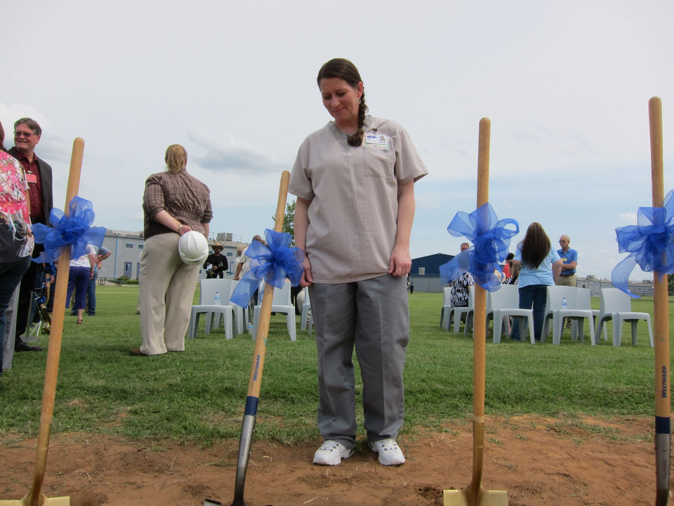 Photo - Mabel Bassett Correctional Center inmate Sheila Hargis looks at ceremonial shovels during the recent groundbreaking ceremony for a new prison chapel to be built at the McLoud prison beginning in September.  Carla Hinton - The Oklahoman