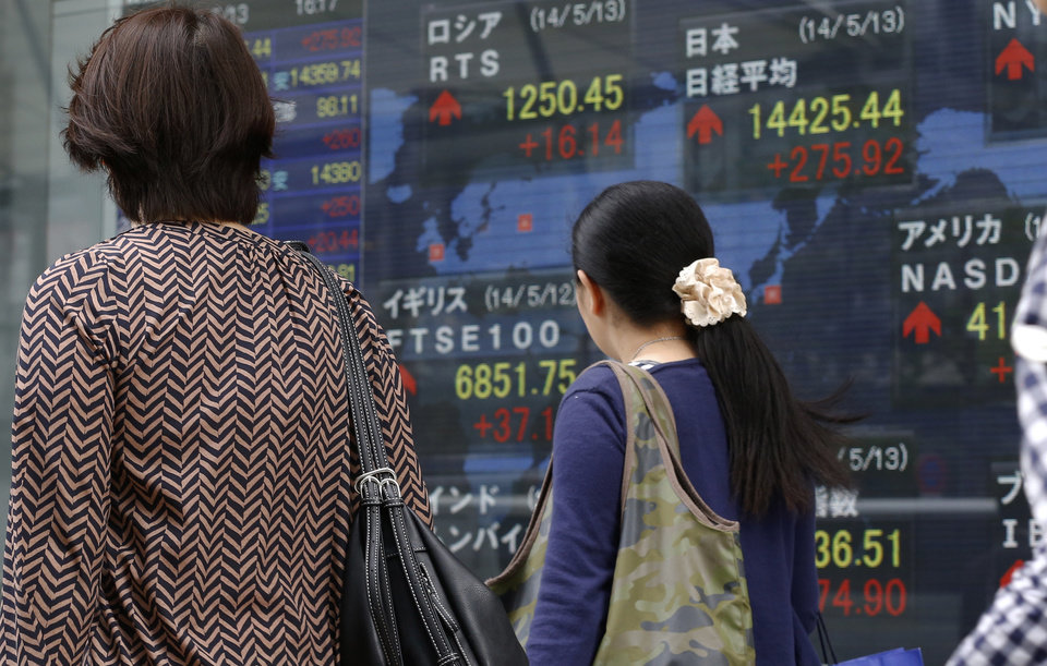 Photo - Women walk past an electronic stock indicator of a securities firm in Tokyo, Tuesday, May 13, 2014. Asian stock markets rose after Wall Street indexes hit record highs, with Japan's Nikkei 225 leading gains as the yen weakened. The Nikkei ended up 275.92 points at 14,425.44 on Tuesday. (AP Photo/Shizuo Kambayashi)