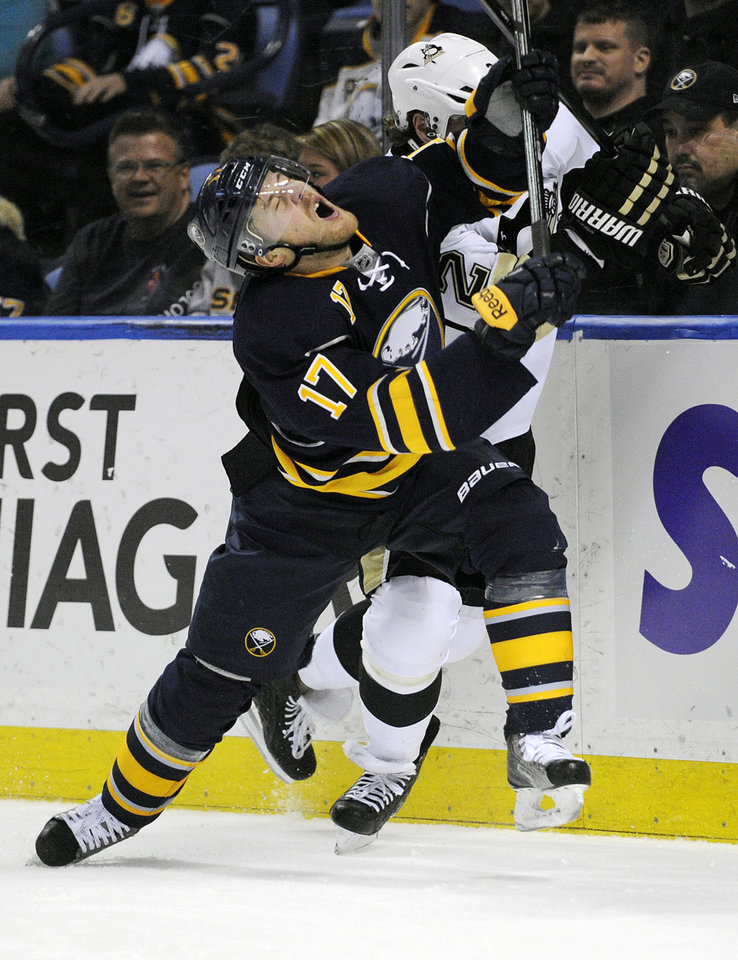 Photo - Buffalo Sabres' Linus Omark (17), of Sweden, reacts to a high stick from  Pittsburgh Penguins' Matt Niskanen, right, during the first period of an NHL hockey game in Buffalo, N.Y., Wednesday, Feb. 5,  2014. (AP Photo/Gary Wiepert)