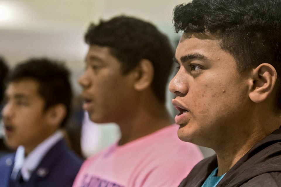 Photo -  Marshall Island students Jebet Mote Jr., Davis Bejang and Freddy Neel, from right, take part in a multicultural choir practice at Enid High School.   [Photo by Chris Landsberger, The Oklahoman]
