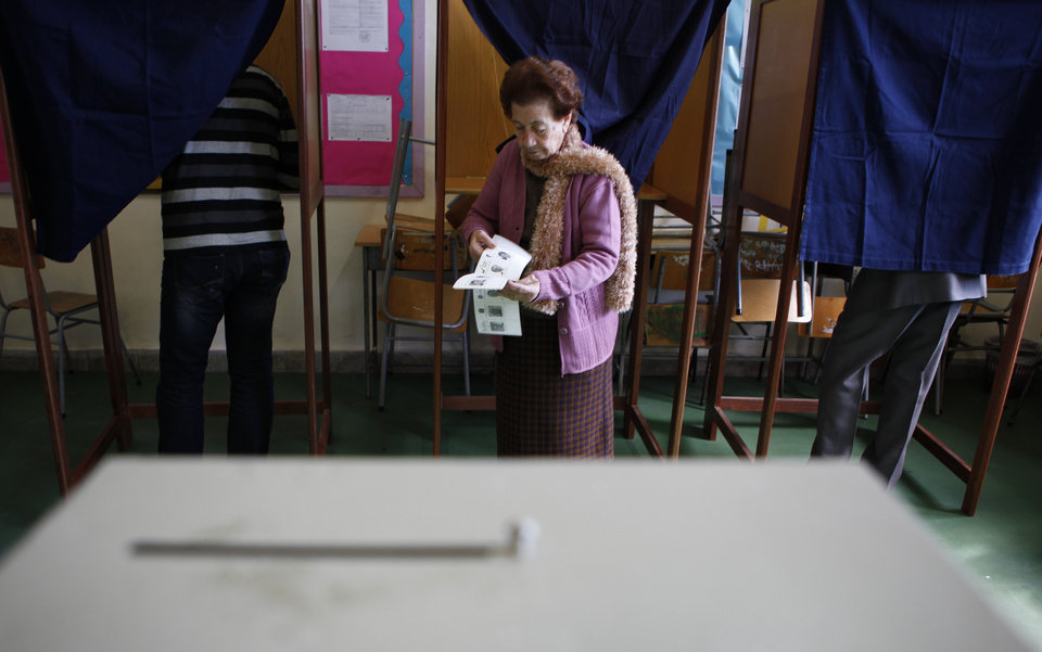 Photo - A woman leaves the polling booth as two men are seen in the booths as they vote in the Presidential election in southern port city of Limassol, Cyprus, Sunday, Feb. 17, 2013. Cypriots vote for a new president to guide them through a severe economic crisis that has the country joining other troubled European nations in seeking international rescue money to pull it back from the brink of bankruptcy. (AP Photo/Petros Karadjias)