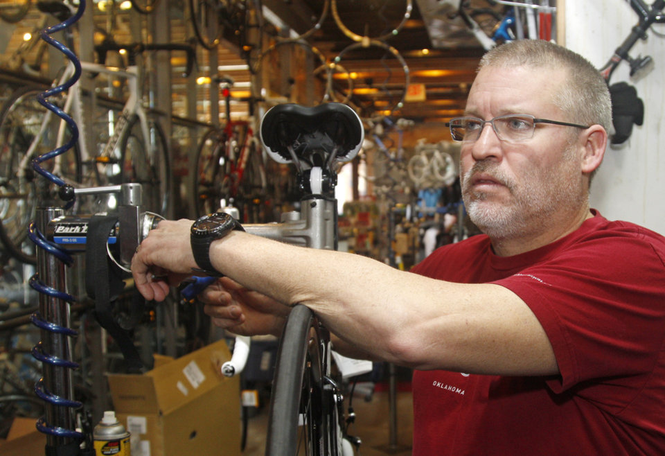 Photo -   Steve Schlegel, owner of Schlegel Bicycles, answers a question while working on a bicycle in the shop's pro shop, in Oklahoma City, Thursday, Jan. 26, 2012. (AP Photo/Sue Ogrocki)