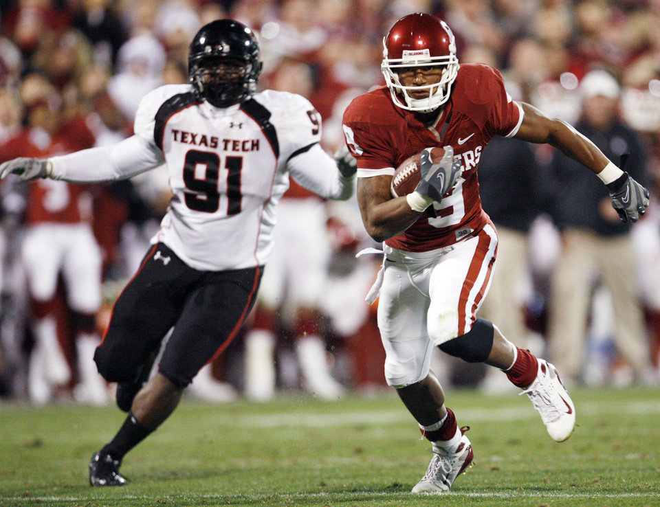 Photo - OU's Juaquin Iglesias (9) breaks away from Rajon Henley (91) of Texas Tech after a catch on the way to a touchdown in the second quarter of the college football game between the University of Oklahoma Sooners and Texas Tech University at Gaylord Family -- Oklahoma Memorial Stadium in Norman, Okla., Saturday, Nov. 22, 2008. BY NATE BILLINGS, THE OKLAHOMAN