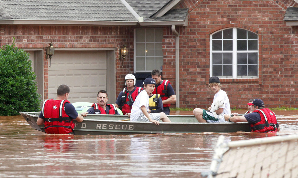 Oklahoma City Fire Department rescue crews take two boys and their dog to higher ground Monday in The Valley addition in the Edmond area after floodwaters inundated a number of homes. Photo By Paul Hellstern, The Oklahoman