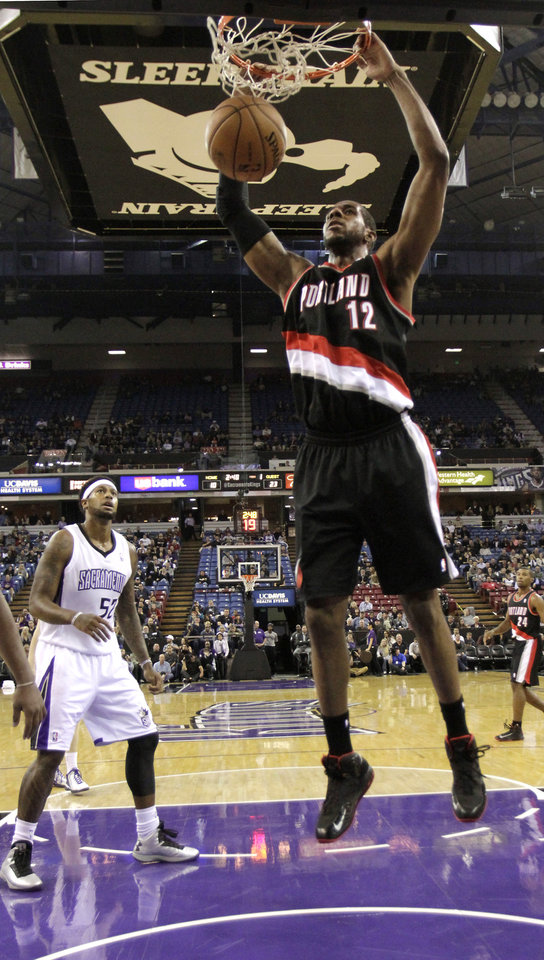 Portland Trail Blazers forward LaMarcus Aldridge, right, hangs on the rim after stuffing the basket as Sacramento Kings forward James Johnson looks on during the first half of an NBA basketball game in Sacramento, Calif., Tuesday, Nov. 13, 2012. (AP Photo/Rich Pedroncelli)