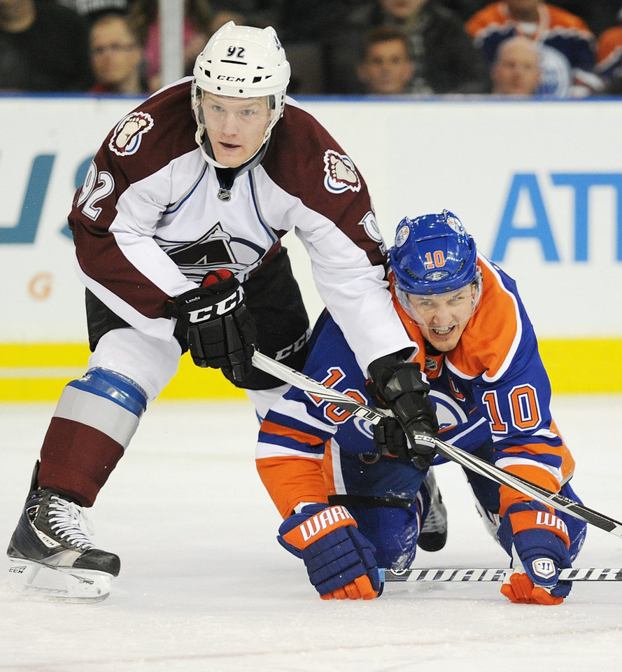 Colorado Avalanche\'s Gabriel Landeskog, left, battles with the Edmonton Oilers\' Shawn Horcoff during the first period of an NHL hockey game in Edmonton, Alberta, on Friday, Dec. 9, 2011. (AP Photo/The Canadian Press, John Ulan)