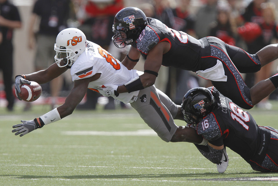 Oklahoma State Cowboys wide receiver Justin Blackmon (81) is brought down by Texas Tech Red Raiders linebacker Zach Winbush (27) and Cody Davis (16) during the college football game between the Oklahoma State University Cowboys (OSU) and Texas Tech University Red Raiders (TTU) at Jones AT&T Stadium on Satruday, Nov. 12, 2011. in Lubbock, Texas. Photo by Chris Landsberger, The Oklahoman ORG XMIT: KOD