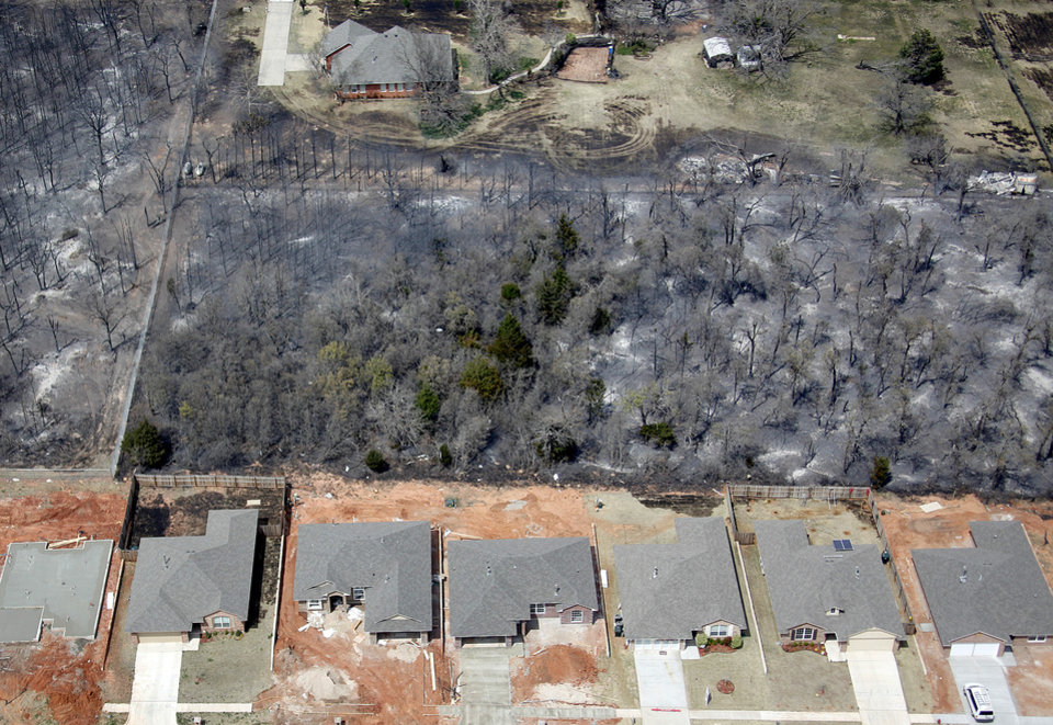 Photo - FIRES / WILDFIRES / HOUSE / DAMAGE/ AFTERMATH: Homes back up to a burned area in Midwest City, Okla., Friday, April 10, 2009. Photo by Bryan Terry, The Oklahoman ORG XMIT: KOD