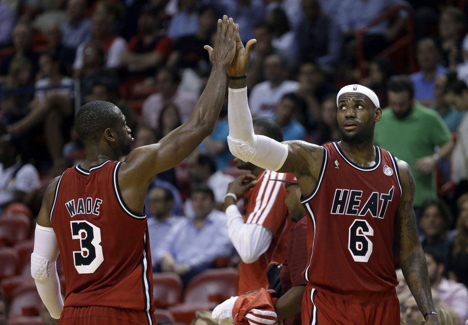 Miami Heat\'s LeBron James (6) high-fives teammate Dwyane Wade (3) as they head to the bench for a timeout during the second half of an NBA basketball game against the Portland Trail Blazers in Miami, Tuesday, Feb. 12, 2013. James became the first player in NBA history to score 30 points and shoot at least 60 percent in six straight games as the Heat defeated the Trail Blazers 117-104. (AP Photo/Alan Diaz)