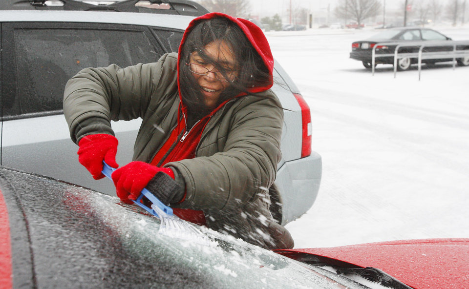 Photo - BLIZZARD / CHRISTMAS EVE / ICE / COLD / WINTER WEATHER / WINTER STORM / SNOWSTORM / SNOW: Target employee Leslie Florez (CQ FLOREZ), scrapes the ice off her windshield at Target, NW Expressway and Rockwell, in Oklahoma City Thursday, Dec. 24, 2009. Photo by Paul B. Southerland, The Oklahoman ORG XMIT: KOD