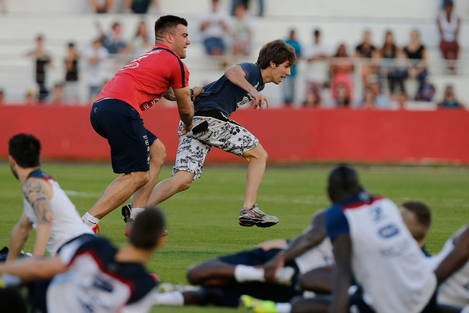 Photo - Cyril Praud, physical therapist for French team, runs after a soccer fan storming the pitch at the end of a training session at the Santa Cruz Stadium, in Ribeirao Preto, Brazil, Friday, June 13, 2014. France will play in group E of the 2014 Brazil soccer World Cup. (AP Photo/David Vincent)