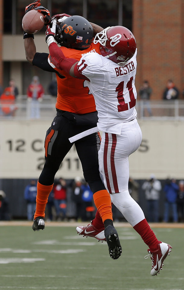 Oklahoma State's Justin Gilbert (4) can't hold on for an interception in front of Oklahoma's Lacoltan Bester (11) during Oklahoma's final drive in the Bedlam college football game between the Oklahoma State University Cowboys (OSU) and the University of Oklahoma Sooners (OU) at Boone Pickens Stadium in Stillwater, Okla., Saturday, Dec. 7, 2013. Oklahoma won 33-24. Photo by Bryan Terry, The Oklahoman