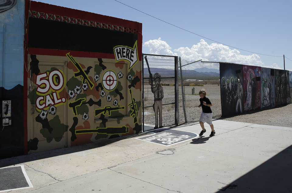 Photo - A young person runs by the Last Stop outdoor shooting range Wednesday, Aug. 27, 2014, in White Hills, Ariz. Gun range instructor Charles Vacca was accidentally killed Monday, Aug. 25, 2014 at the range by a 9-year-old with an Uzi submachine gun. (AP Photo/John Locher)