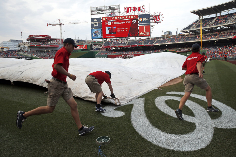 Photo - The Washington Nationals grounds crew works to cover the field before an interleague baseball game against the Baltimore Orioles at Nationals Park, Tuesday, July 8, 2014, in Washington. (AP Photo/Alex Brandon)