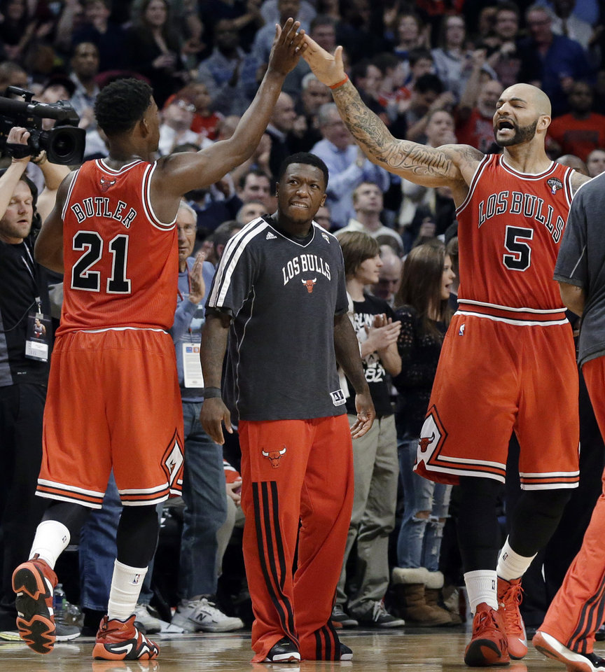Photo - Chicago Bulls guard Jimmy Butler, left, celebrates with forward Carlos Boozer after scoring a basket, as Nate Robinson, center, watches during the second half of an NBA basketball game against the Miami Heat in Chicago on Wednesday, March 27, 2013. The Bulls won 101-97, ending the Heat's 27-game winning streak. (AP Photo/Nam Y. Huh)