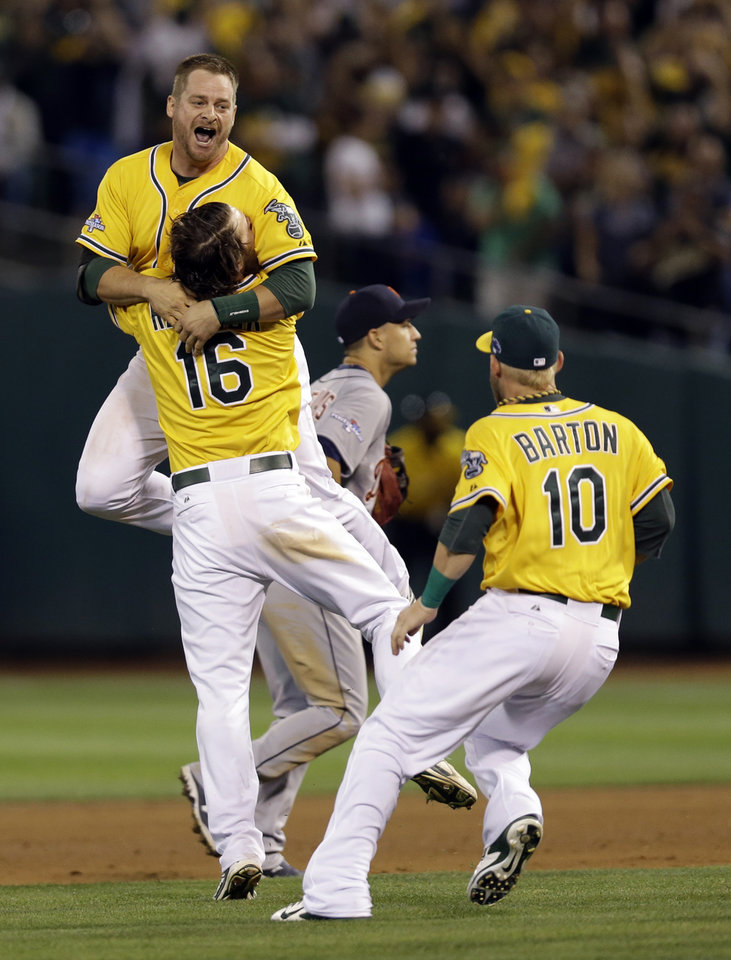 Oakland Athletics Stephen Vogt is lifted up by teammate Josh Reddick as Daric Barton moves in to celebrate Vogt's game winning hit in the bottom of the ninth inning of Game 2 of an American League baseball Division Series against the Detroit Tigers in Oakland, Calif., Saturday, Oct. 5, 2013. (AP Photo/Marcio Jose Sanchez)