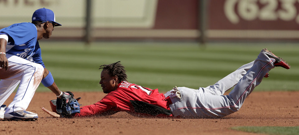 Cincinnati Reds' Emmanuel Burriss, right, is tagged out by Kansas City Royals shortstop Alcides Escobar as he is caught stealing during the third inning of an exhibition spring training baseball game on Friday, March 1, 2013, in Surprise, Ariz. (AP Photo/Charlie Riedel)