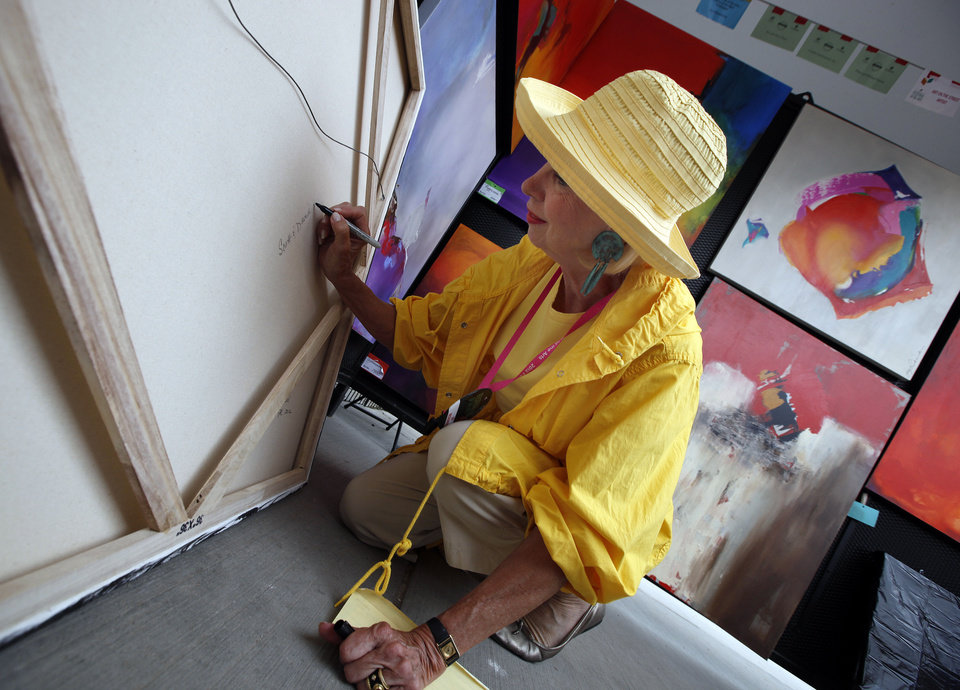 Joy Richardson signs a painting during the the Festival of the Arts in Oklahoma City, Sunday, April 29, 2012. Photo by Sarah Phipps, The Oklahoman
