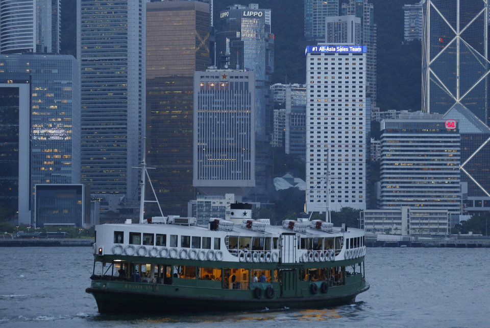 """In this July 17, 2014 photo, a star ferry sails across Chinese People\'s Liberation Army Forces Hong Kong Building, center in the background, at the Hong Kong\'s Victoria Harbor. As skyscrapers around Hong Kong harbor erupted into a reverie of laser beams and giant digital displays, one innocuous 28-story building near the water's edge had stayed dark for months, clad in bamboo scaffolding for a face-lift. Then, in June, the renovated tower came to life, flashing giant Chinese characters that some in Hong Kong saw as a warning.""""People's Liberation Army,"""" it said. (AP Photo/Kin Cheung)"""