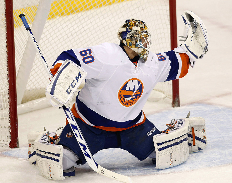 Photo - New York Islanders goalie Kevin Poulin makes a glove save against the Minnesota Wild during the first period of their NHL hockey game, Sunday, Dec. 29, 2013, in St. Paul, Minn.(AP Photo/Andy Clayton-King)