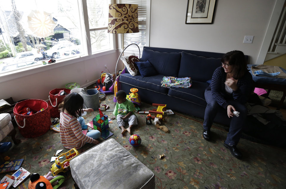 Photo - EMBARGOED UNTIL MIDNIGHT EASTERN TIME SUNDAY, FEB. 17 - Nancy Jensen, right, watches as her children, Elizabeth, 6, left, and Joe, 2, center, play with a building set and other toys, Tuesday, Feb. 12, 2013 at their home in Seattle. Nancy was a participant in a new University of Washington study on the effects of television viewing on kids that will be published Monday, Feb. 18, 2013. As a result of what she learned, her children spend more time with hands-on toys and less time watching TV. (AP Photo/Ted S. Warren)