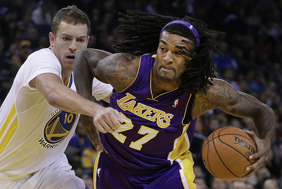 Photo - Los Angeles Lakers' Jordan Hill, right, drives the ball against Golden State Warriors' David Lee during the first half of an NBA basketball game Saturday, Dec. 21, 2013, in Oakland, Calif. (AP Photo/Ben Margot)