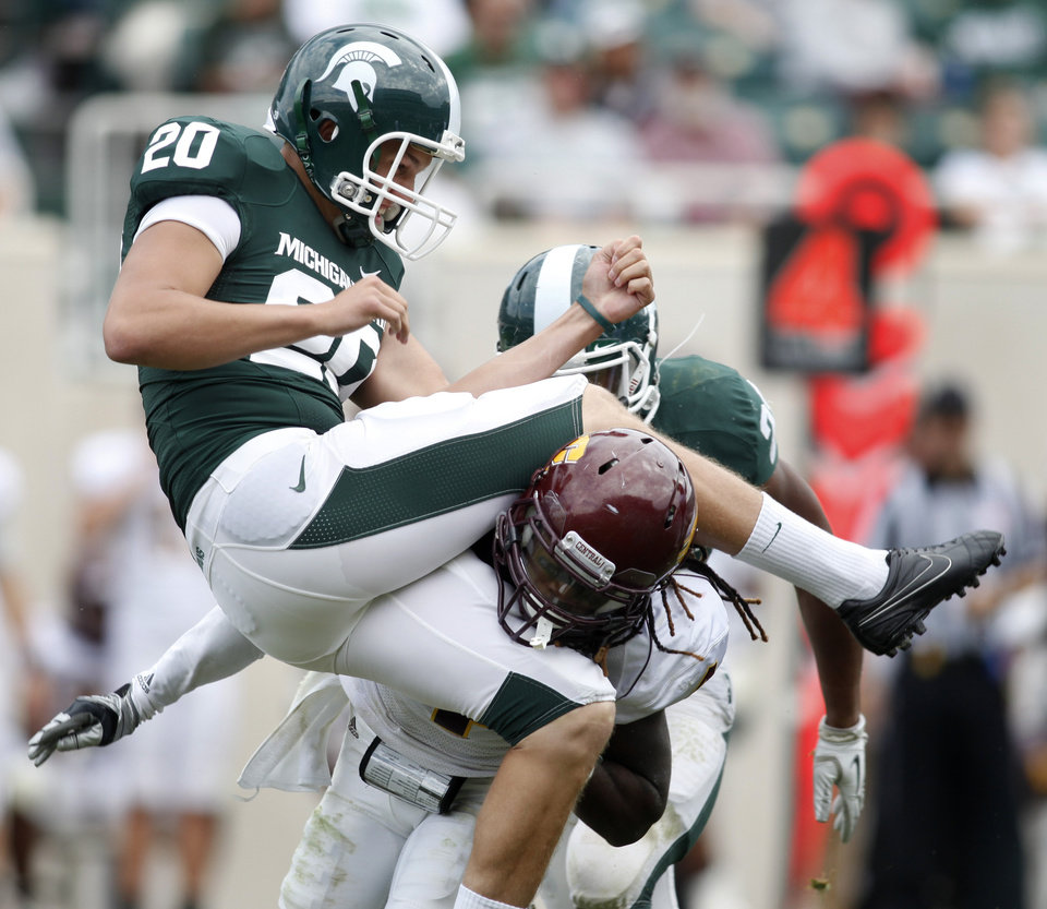 Photo -   Michigan State punter Kyle Selden (20) and Central Michigan defensive back Jahleel Addae get tangled up on a punt during the fourth quarter of an NCAA college football game, Saturday, Sept. 24, 2011, in East Lansing, Mich. Central Michigan was flagged for roughing the kicker. Michigan State won 45-7. (AP Photo/Al Goldis)
