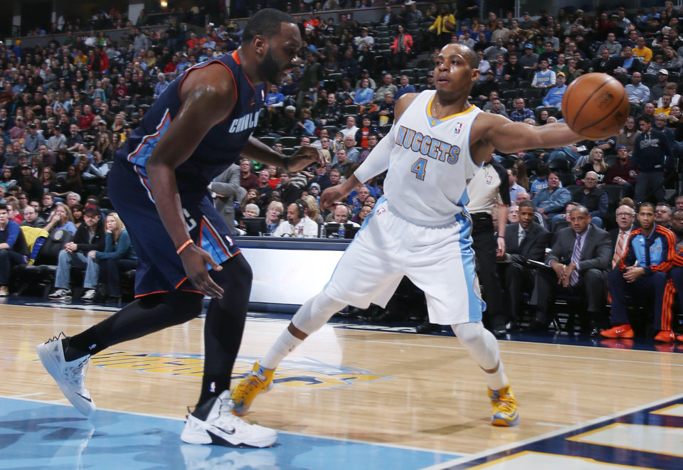 Photo - Denver Nuggets guard Randy Foye, right, reaches out to pull in a loose ball as Charlotte Bobcats center Al Jefferson covers in the first quarter of an NBA basketball game in Denver on Wednesday, Jan. 29, 2014. (AP Photo/David Zalubowski)