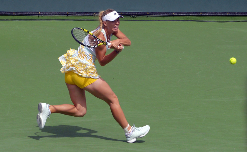 Photo - Caroline Wozniacki, of Denmark, volleys with Jelena Jankovic, of Serbia, in their fourth round match at the BNP Paribas Open tennis tournament, Tuesday, March 11, 2014, in Indian Wells, Calif. (AP Photo/Mark J. Terrill)