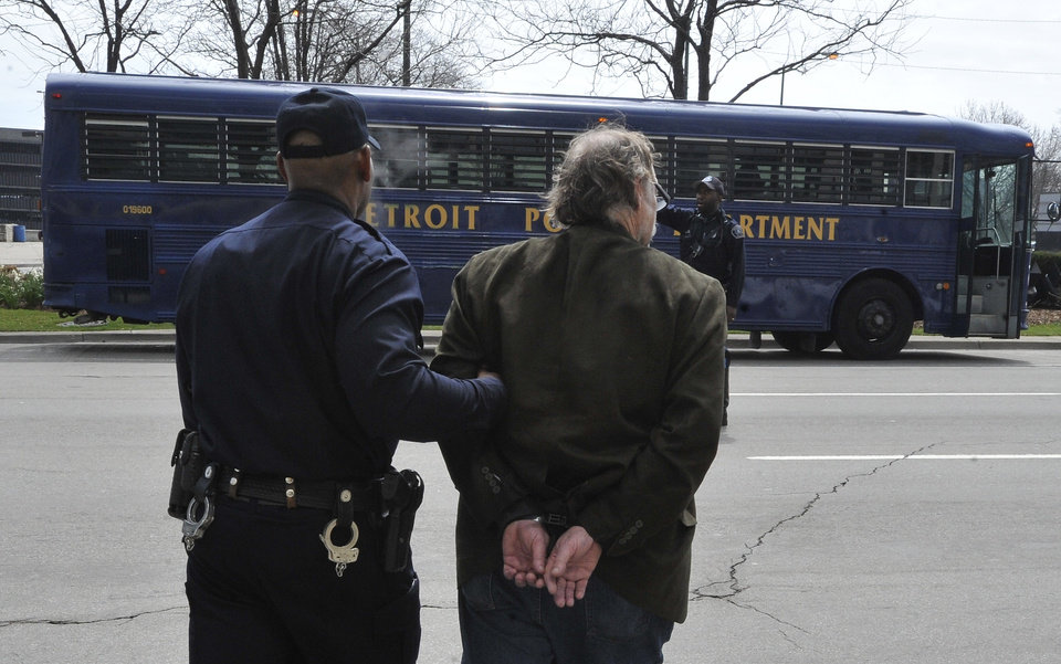 "Photo - FILE - In this April 16, 2013, file photo a Detroit Police officer escorts a man in handcuffs in Detroit.  A 41-page report filed Monday, May 13, 2013, by Detroit's emergency manager doesn't use the word ""bankruptcy,"" but it's clear about one thing: The city is broke and needs a massive infusion of cash or severe penny-pinching to avoid a filing and further reduction in already-crumbling city services, according to experts monitoring the ongoing fiscal dilemma.   (AP Photo/The Detroit News, Daniel Mears, File)"