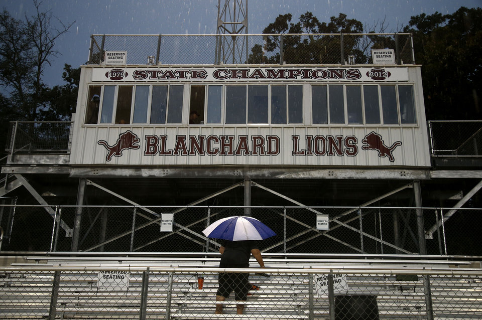 Photo - A fan waits for the rain to stop during a weather delay before a high school football scrimmage between Blamchard and Kingfisher in Blanchard, Okla., Thursday, August 28, 2014. Photo by Bryan Terry, The Oklahoman