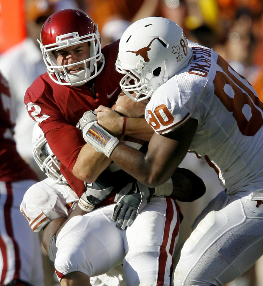 Photo - OU's Landry Jones is brought down b y Sam Acho, left, and Alex Okafor of Texas during the second half of the Red River Rivalry college football game between the University of Oklahoma Sooners (OU) and the University of Texas Longhorns (UT) at the Cotton Bowl on Saturday, Oct. 2, 2010, in Dallas, Texas. OU defeated Texas 28-20.   Photo by Bryan Terry, The Oklahoman