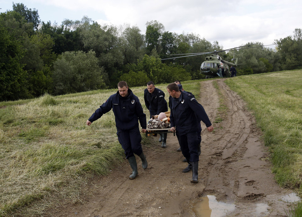 Photo - Serbian police officers carry an old man from a military helicopter during flood evacuation from Obrenovac, some 30 kilometers (18 miles) southwest of Belgrade Serbia, Saturday, May 17, 2014. Record flooding in the Balkans leaves at least 20 people dead in Serbia and Bosnia and is forcing tens of thousands to flee their homes. Meteorologists say the flooding is the worst since records began 120 years ago. (AP Photo/Darko Vojinovic)