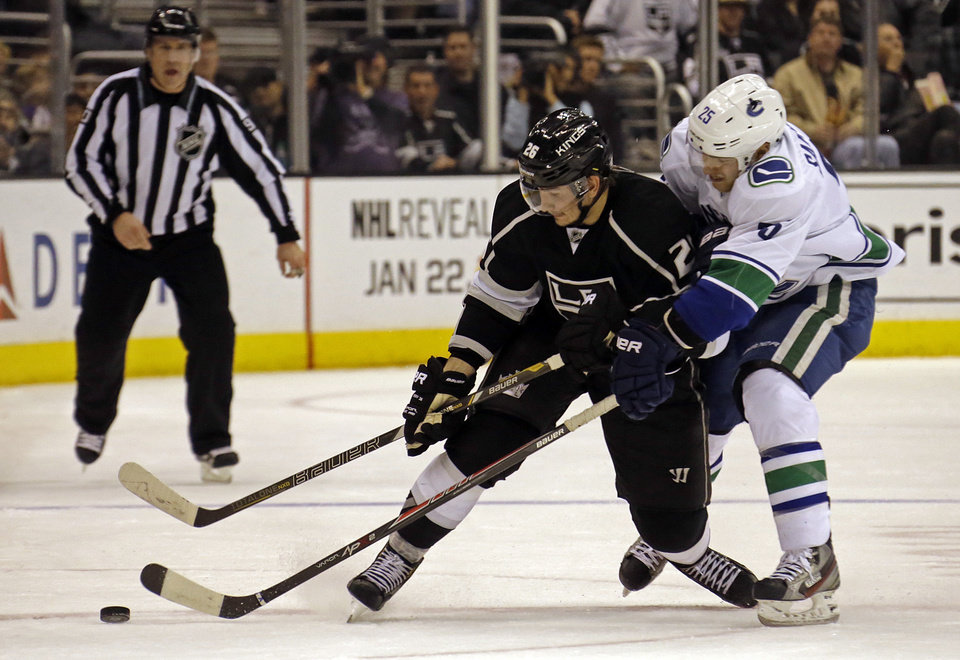 Photo - Vancouver Canucks center Mike Santorelli (25), right, and Los Angeles Kings defenseman Slava Yoynov (26), of Russia, battle for the puck in the second period of an NHL hockey game in Los Angeles Monday, Jan. 13, 2014.  (AP Photo/Reed Saxon)