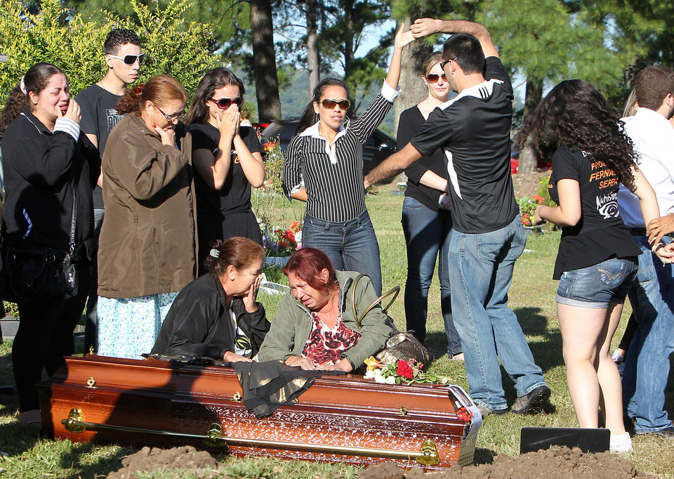 Relatives and friends dance and mourn next to the coffin during the burial of fire victim Tanise Cielo, at a cemetery in Santa Maria city, Rio Grande do Sul state, Brazil,  Monday,  Jan. 28, 2013. The city in southern Brazil started burying the 233 people killed in Sunday's fire at the Kiss nightclub after the conflagration caused by a band's pyrotechnic display. An early investigation into the tragedy revealed that security guards briefly prevented partygoers from leaving through the sole exit. And the bodies later heaped inside that doorway slowed firefighters trying to get in.(AP Photo/Nabor Goulart)