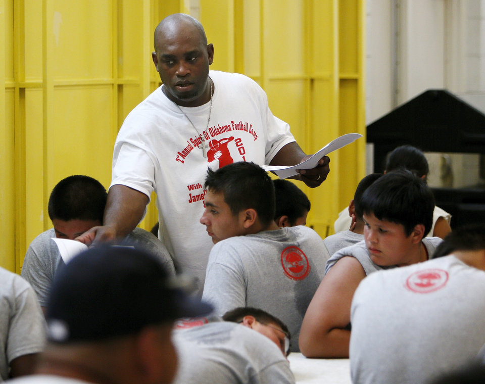 Photo - Former OU quarterback Jamelle Holieway passes out health and safety information provided by the Creek Nation during Holieway's Spirit of Oklahoma football camp in Weleetka, Okla., Friday, July 6, 2012. Photo by Nate Billings, The Oklahoman