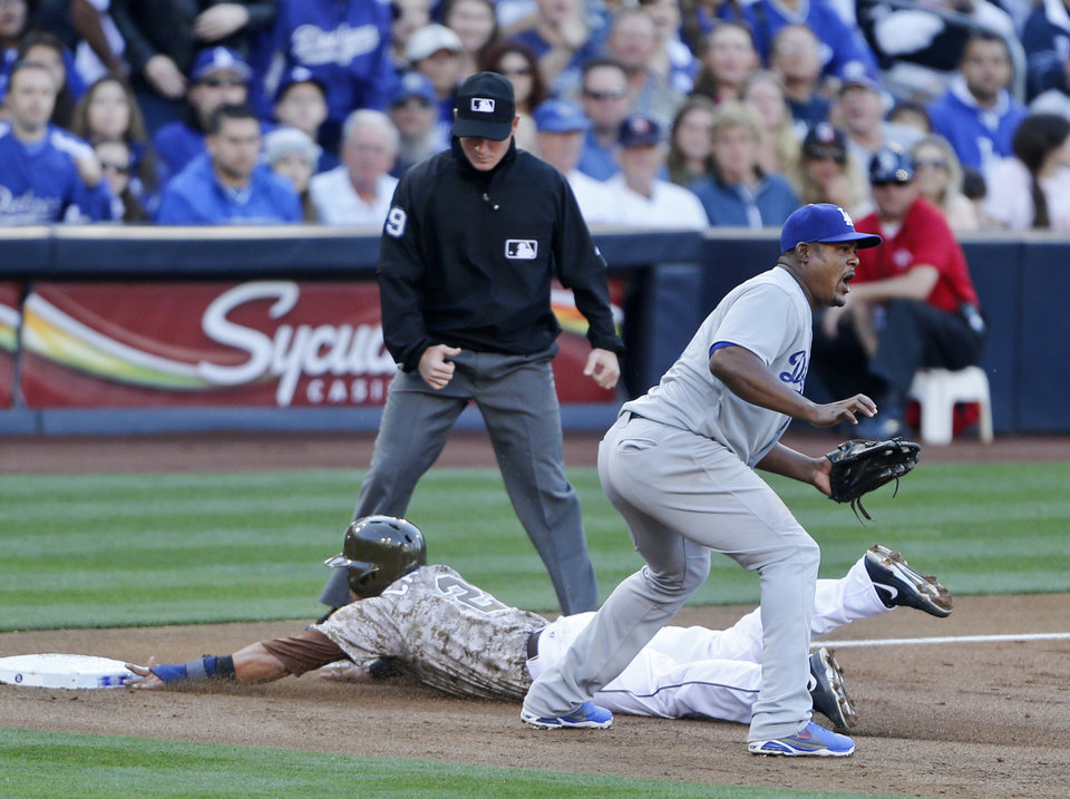 Photo - San Diego Padres' Everth Cabrera slides into third safely as Los Angeles Dodgers third baseman Juan Uribe awaits a late throw in the first inning of the opening game of Major League baseball in the United States Sunday, March 30, 2014, in San Diego.  (AP Photo/Lenny Ignelzi)