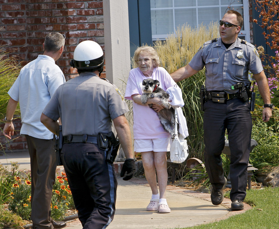 Photo - Oklahoma City Police officers help a resident evacuated from her home in the Apple Valley housing addition on Tuesday, Aug. 30, 2011, in Edmond, Okla. 
