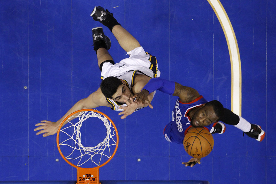 Photo - Philadelphia 76ers' Tony Wroten, right, goes up to shoot against -Utah Jazz's Enes Kanter during the first half of an NBA basketball game on Saturday, March 8, 2014, in Philadelphia. (AP Photo/Matt Slocum)