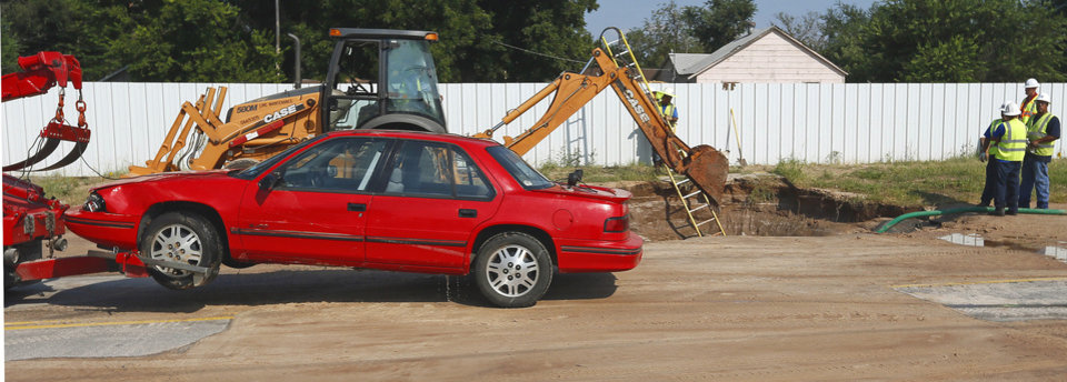 A car is towed away after being removed from a sinkhole that formed when a water main broke at NW 2nd and Villa in Oklahoma City, Thursday, Sept. 5, 2013. Photo by Nate Billings, The Oklahoman