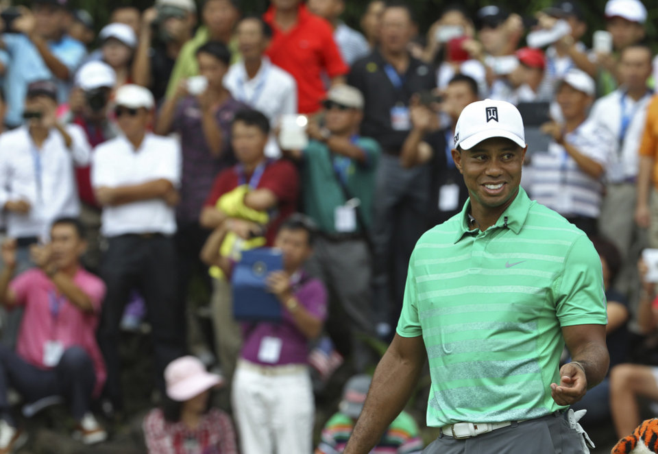 Photo - Tiger Woods of the United States smiles during an exhibition golf match against Rory Mcllory of Northern Ireland in Haikou, in southern China's island province Hainan, Monday, Oct. 28, 2013. (AP Photo/Vincent Yu)