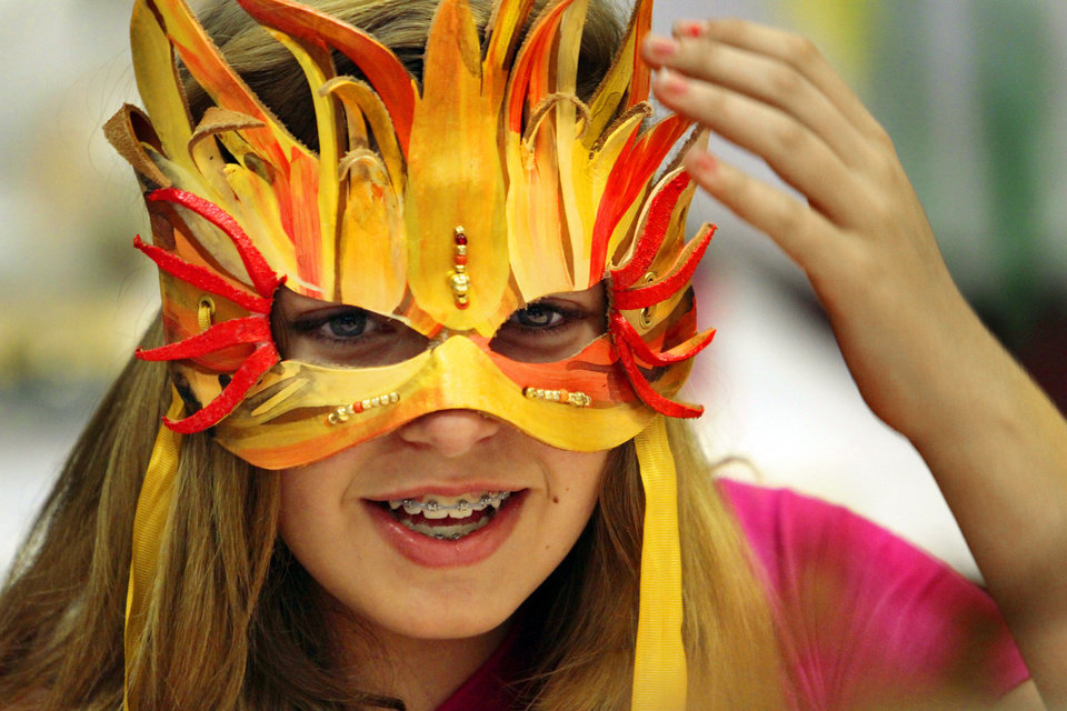Photo - Jessica Riley, 12, tries on a mask made by Patrick Riley as he leads a workshop in mask making at the Norman Public Library on Tuesday. Photos by Steve Sisney, The Oklahoman