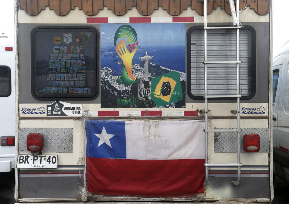 Photo - A motorhome decorated with a Chilean flag and World Cup poster showing a photo of Christ the Redeemer sits parked in the Terreirao do Samba area of Rio de Janeiro, Brazil, Saturday, June 21, 2014. Some soccer fans who came for the World Cup in recreational vehicles were relocated from Copacabana beach to this area designed for events during carnival. (AP Photo/Silvia Izquierdo)