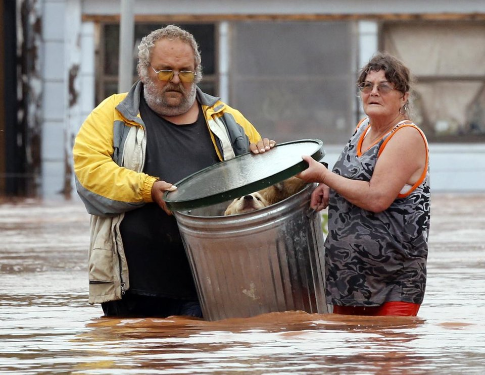 Photo - George and Susan Kruger make one of three trips with their animals from their flooded house to safety on Sunday, May 24, 2015 in Purcell, Okla.  Rising water from overnight rains began to rise early in the morning.  The Krugers refused to leave their home and made several trips to retrieve five dogs and a baby chick.    (Steve Sisney/The Oklahoman via AP)