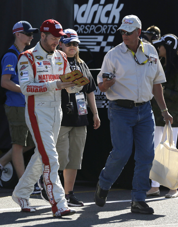 Photo - Dale Earnhardt Jr. signs autographs in the garage area during a practice session for Sunday's NASCAR Sprint Cup Series auto race at Pocono Raceway on Saturday, June 7, 2014, in Long Pond, Pa. (AP Photo/Mike Groll)