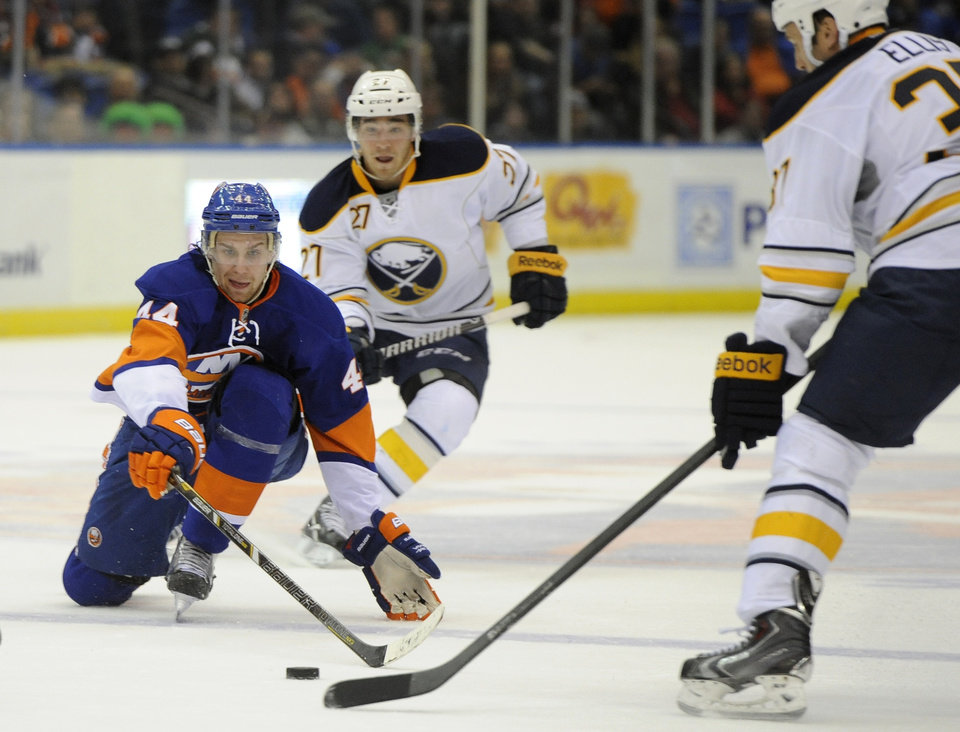 Photo - New York Islanders defenseman Calvin de Haan (44) goes down the ice to chase the puck away from Buffalo Sabres' Matt D'Agostini (27) and Matt Ellis (37) in the second period of an NHL hockey game on Saturday, March 15, 2014, in Uniondale, N.Y. (AP Photo/Kathy Kmonicek)